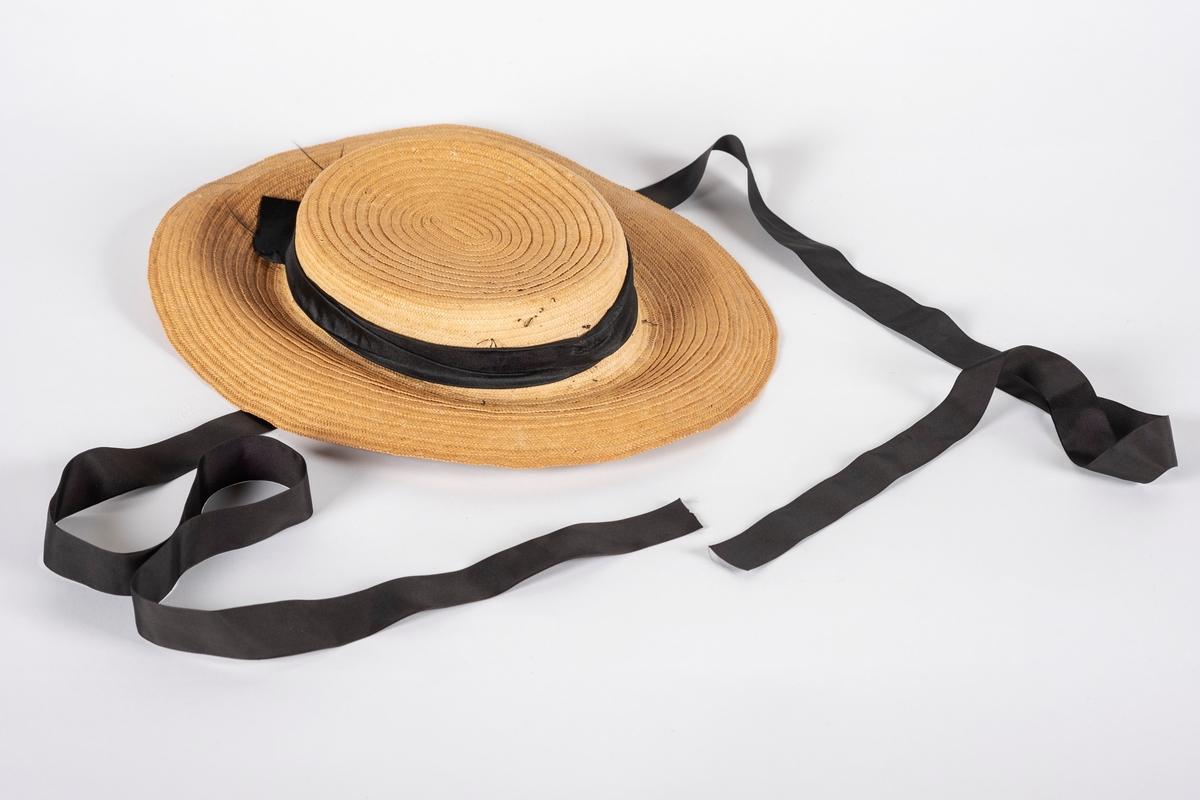 Naturfarget, oval stråhatt med sort pyntebånd rundt pullen. Undersiden av bremmen er fòret med fløyel. Under fòret er bremmen stivet av med en ståltråd. Hvit og blåstripet svettebånd av bomull. Svarte hakerem.
