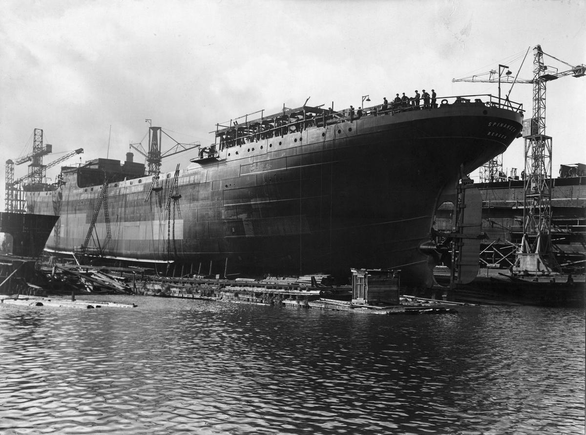 Motivet viser MT SPINANGER (bygget i 1927) under bygging ved Schiechau i Gdansk. Arbeidsfolk på dekk og havnekraner i bakgrunnen.