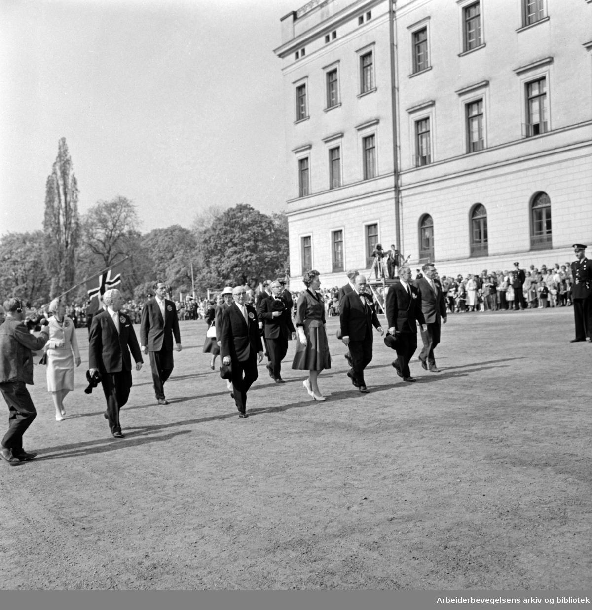 17. mai-komiteén fotografert utenfor slottet. Blant andre: Olav Brunvand, Brynjulf Bull, Rolf Stranger, Eva Kolstad og Olaf Solumsmoen. 17. mai 1960.