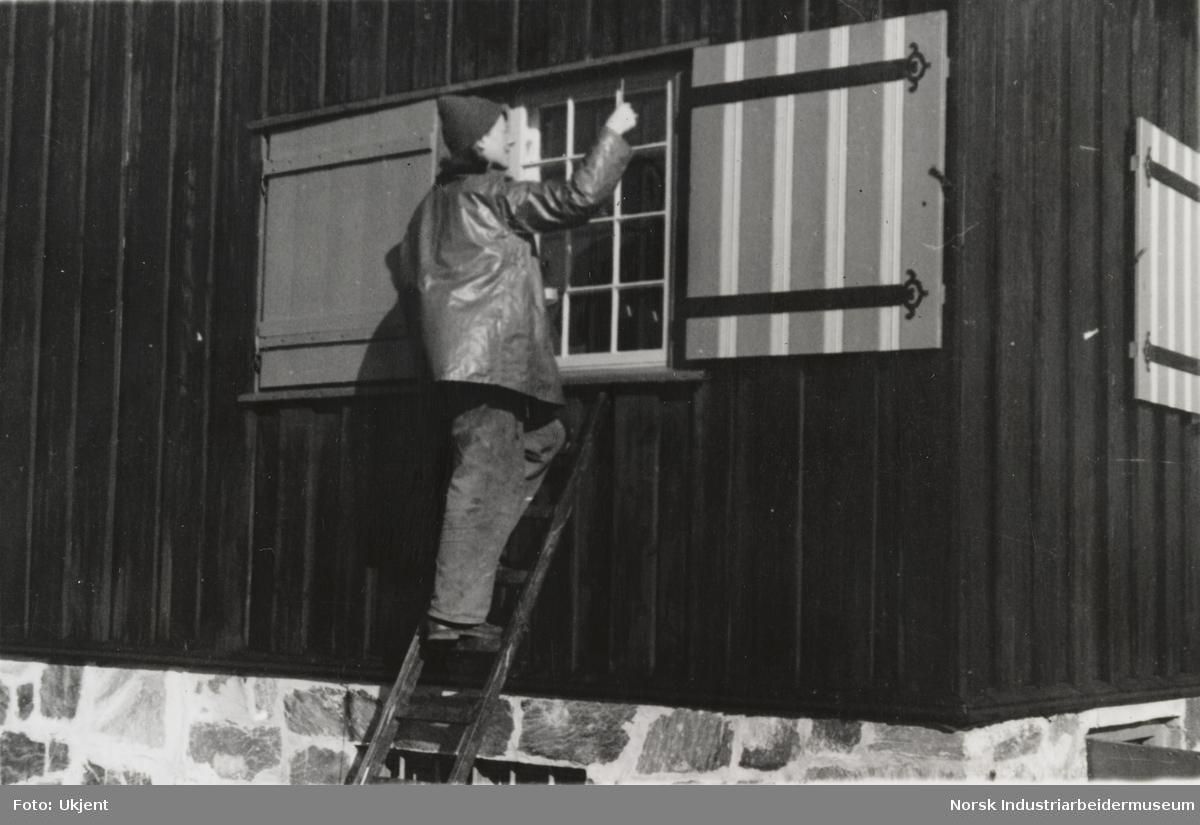 Unni Coward står på stige mot vindu på husfasade, Sundet, Møsstrond