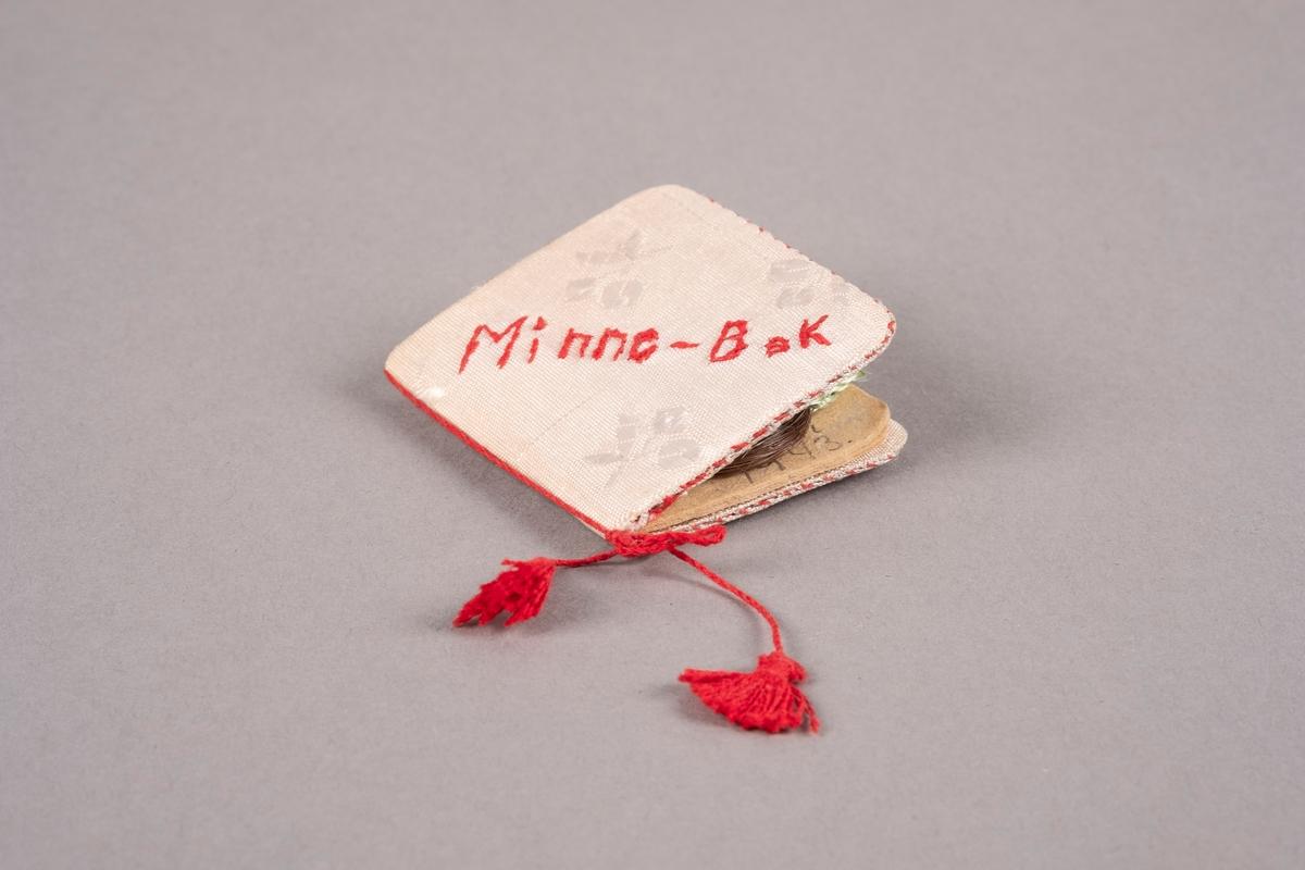 """En minnebok med omslag av papp kledd med tekstil med blomstermønster. En tråd med to dusker er knyttet rundt ryggen. """"Minne-Bok"""" er brodert på framsiden. Inne i minneboken ligger en hårlokk bundet med grønn tråd."""