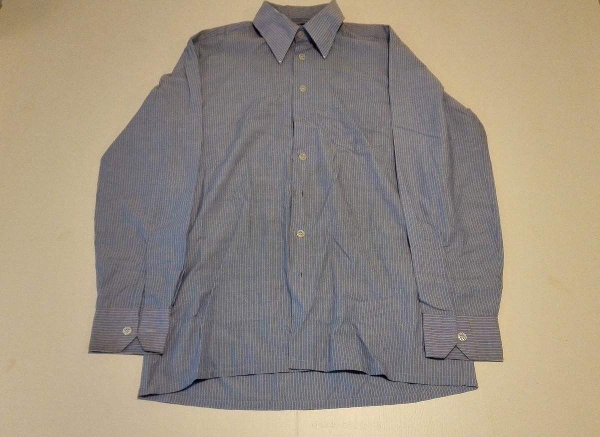 Forknappa, 1 lomme, spiss skjortekrage.  Har langt erme med fast mansjett.