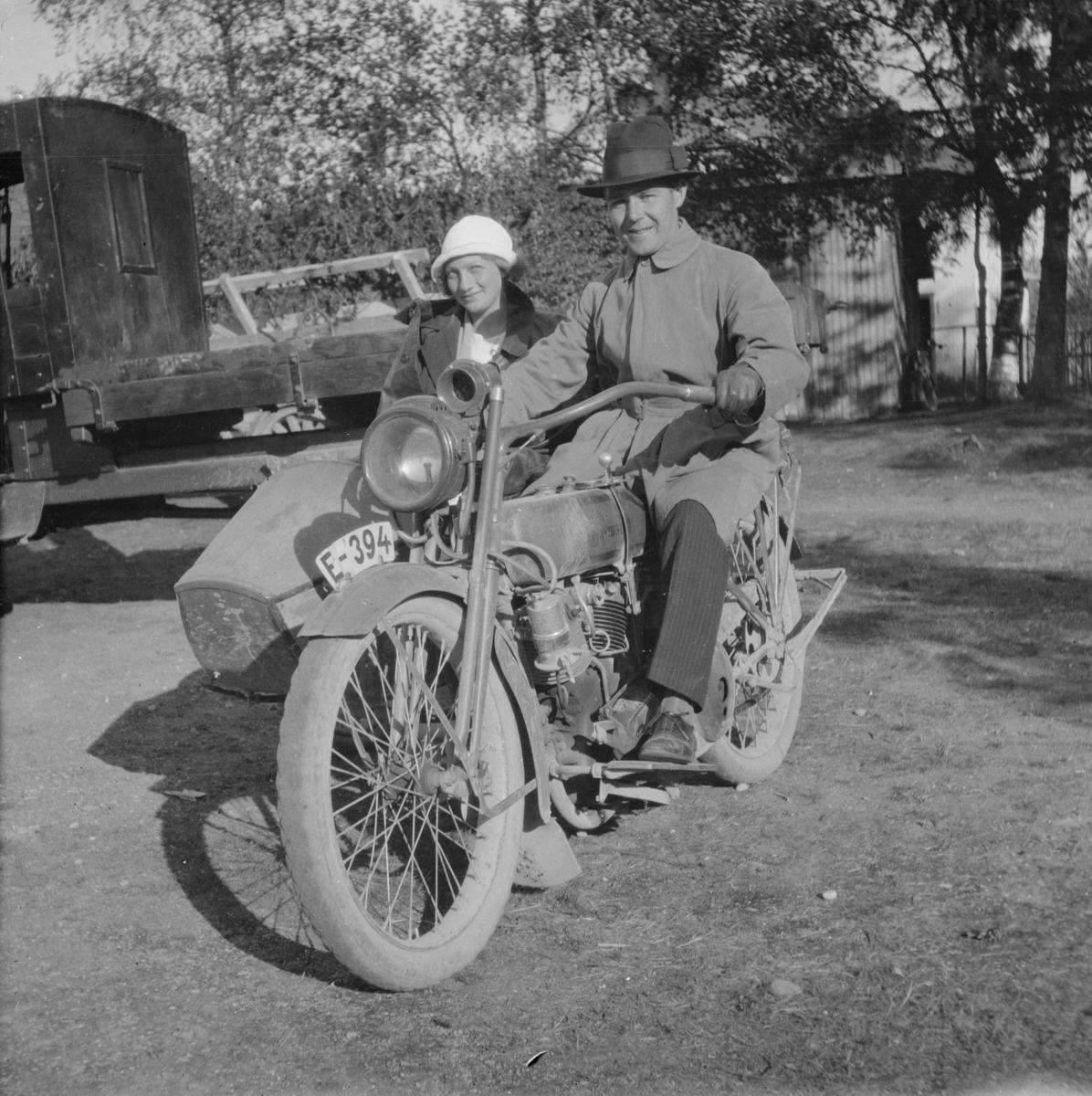 Kvinne og mann på motorsykkel med sidevogn.