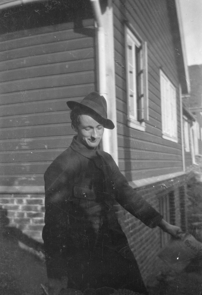 Portrett av ung mann i hatt utenfor en bygning.
