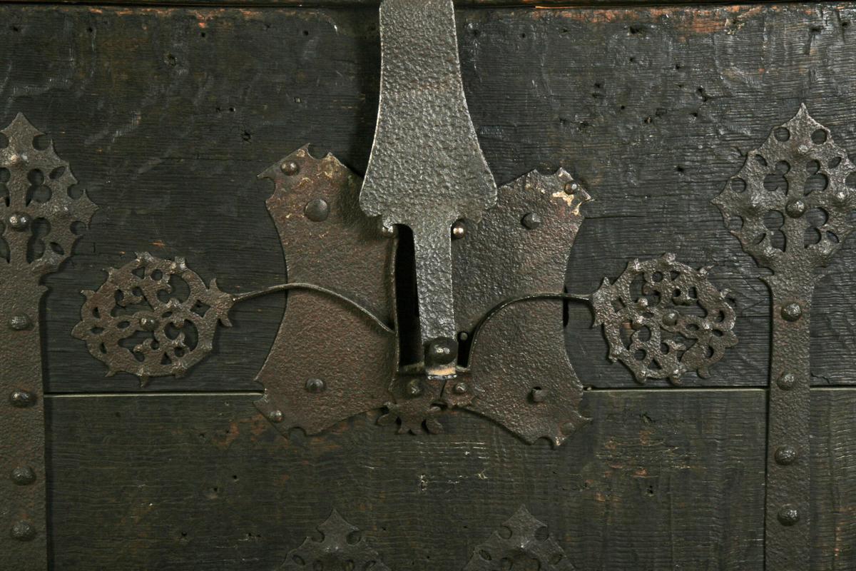 Eik, smijern. Rette sider og lokk. Forlengete stående ekebord på langsidene tjener som føtter. Sider og lokk dekorert med delvis ornamentert smijern. Treverket sterkt medtatt. Restaurert.