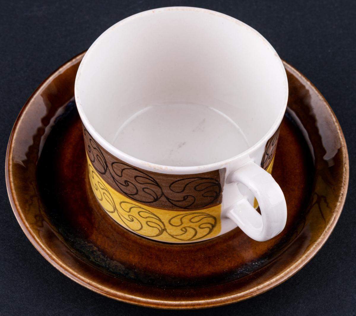 Kaffekopp med fat, modell EH i dekoren Ek. Runt koppen ett brunt och ett gult band med centrumtryck, fatet helt i brunt.
