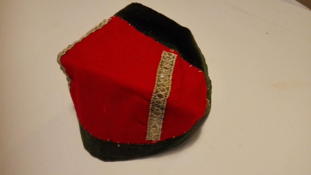 1 barnehue.  Av rødt klæde, foret med hvit strie, kantet med grøn fløiel. Har paasydd to tversgaaende sølvlidser. Gave fra Ingebrigt Andersen Rislag, Vik.