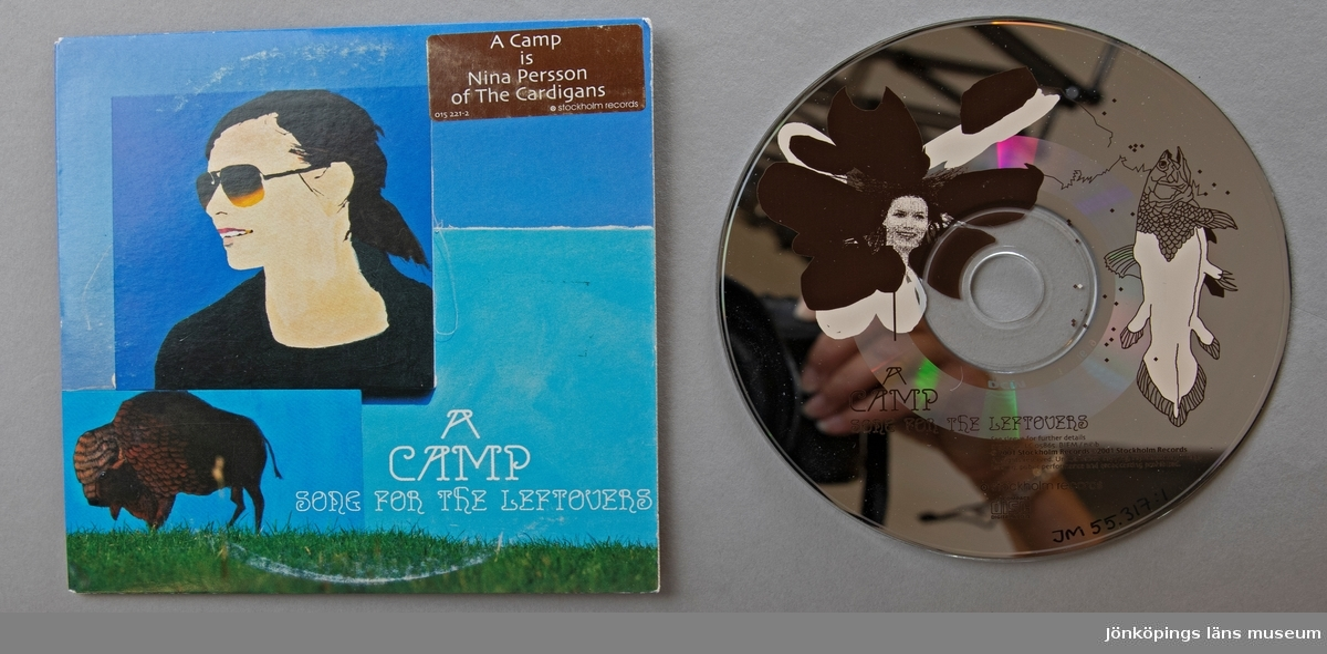CD-skiva, musik med gruppen A Camp med Nina Persson. Skiva i pappkonvolut.  Innehåll: 1. Song for the Leftovers 2. Train for salvation  JM 55317:1, Skiva JM 55217:2, Konvolut