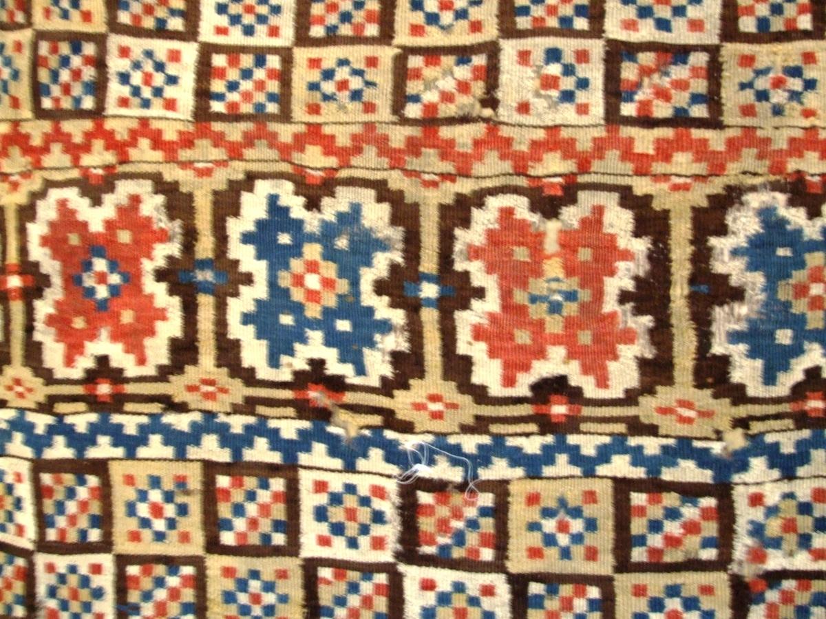 Eit teppe med 4 hovudmotiv. 1. Ruter/romber med blomsterbladsmotiv. (øverst) 2. Ruter annakvar brune og kvite med rutemøster inni. (nest øverst og nedanfor motiv 3) 3. Ei rekkje blomsterbladsmønster litt ovanfor midten 4. Store runde sirkelmotiv med korsmønster inni. Nederst og mellom rekkene finn du i tillegg ein del sikksakkmønster av ulike slag.