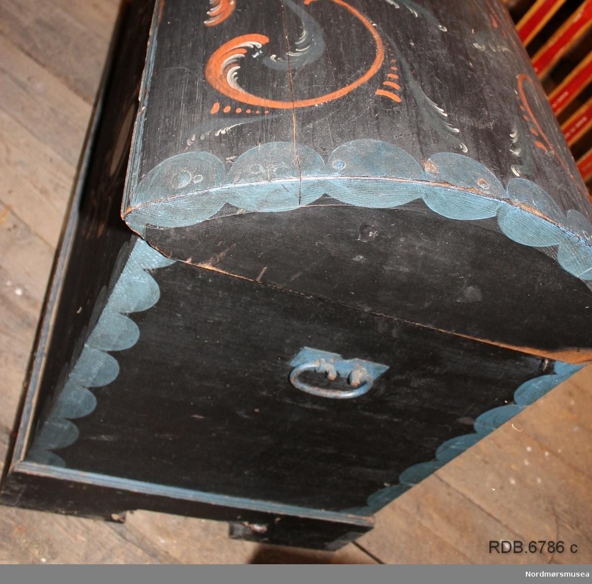 """Stor trekiste med buet lokk malt i en blåsvart farge. Kista står på en løs sokkel som er sinket sammen i hjørnene. Sidene på kista er også sinket sammen. Kista har jernhåndtak på sidene. Lokket er hengslet til kista med jernhengsler, Beslag rundt nøkkelhullet er også i jern, dette er blåmalt. Nøkkel mangler. Kista er dekorert med et blått """"bølgemønster"""" langs hjørnene og tvers over lokket. Ellers rosemalt både på lokk og framside. Foran er det to kvite, runde felt på hver side av midten med monogram i det ene og årstall i det andre. Rundt disse feltene er det rosemaling."""