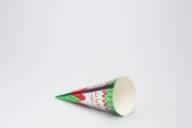 Kjegleformet iskrempapir (kremmerhus) i aluminium og papir. Kremmerhuset er med farger på utsiden, og uten farge (hvit) på innsiden. Kremmerhuset har sølv bakgrunnsfarge med grønt og rødt mønster øverst og nederst som ser ut som blader og blomster. Det er tekst på papiret i et annet skriftspråk.