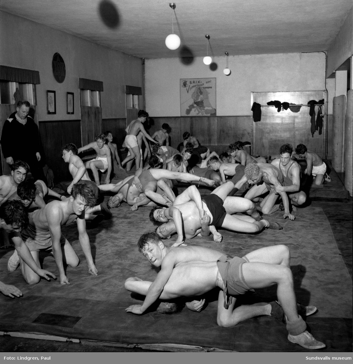 """SAIK idrottsförening, ungbrottare under träning. Tränaren till vänster heter """"Ludde"""" Lindblom. Träningslokalen var förlagd till Grönborgs på andra våningen (i fastigheten fanns även Yrkesskolan)."""