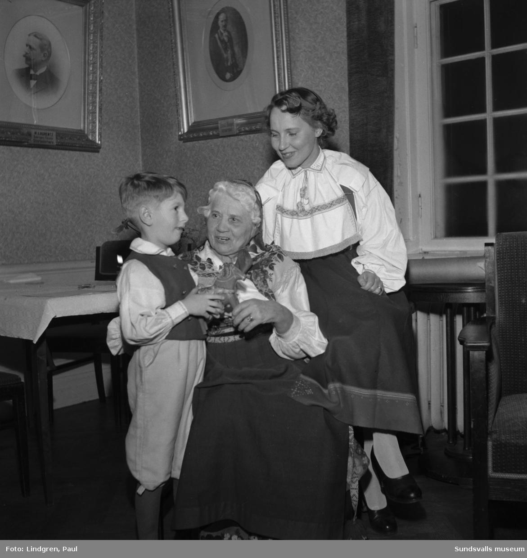 """Julfest på Odd Fellow. Västmanlands Dalagille var arrangör för festen som bestod av tal till hembygden, två sångpjäser """"Betlehems stjärna"""" och """"Trummare tre"""", allsång och jullekar. Jultomten delade ut julklappar till de små och julmat serverades. På bild 1 ses från vänster Elisabeth Mattson, fru Astrid Hållbus och fröken Karin Hållbus. På bild 5 ses """"hans majestät"""" Birger Wallentin."""