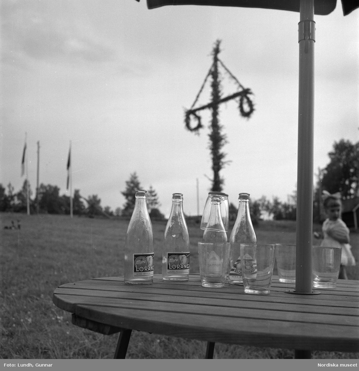 """Motiv: (ingen anteckning) (Lerdalshöjden) ; Tre män spelar fiol vid en midsommarstång, vuxna och barn dansar kring en midsommarstång, en pojke och en kvinna står på en balkong, en flicka - en man och en kvinna sitter vid ett trädgårdsbord under ett parasoll och äter, tomma flaskor av """"Loranga"""" står på ett trädgårdsbord med en midsommarstång i bakgrunden."""
