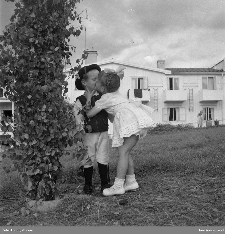 """Motiv: midsommarfirande i Rättvik - Leksand ; En pojke i folkdräkt och en flicka står vid en midsommarstång, en flicka pussar en pojke, en kvinna och en man handlar trasmattor av en man i en försäljningsvagn med text """"Hemslöjd"""", en kvinna står vid en bil med kopparsaker till försäljning och en skylt """"Ruben I Redin"""", en kvinna och en man i folkdräkt håller lövade ringar, kvinnor i folkdräkt går på en väg, en man kör en hästdragen vagn, ett led av kvinnor och män i folkdräkt bär en lövad girlang, människor åker på hästdragna vagnar."""