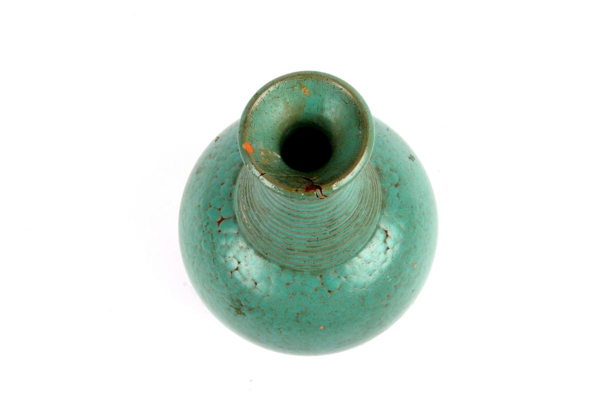 Grønn vase med smal hals.