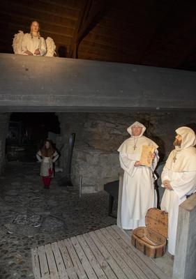En engel ser ned på to munker som selger avlatsbrev.