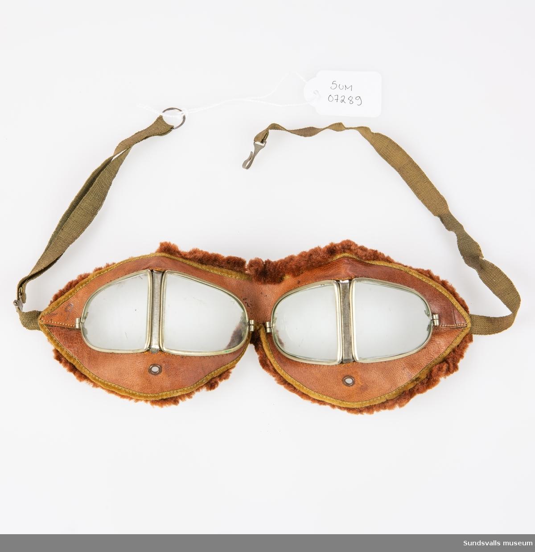 Glasögon i brunt läder med plastlinser. Brun resårrem.