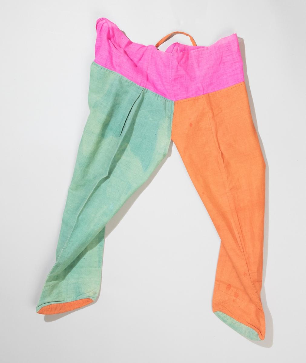 Barnbyxor av bomull med fötter, öppna i grenen. Ena benet är grönt med orange sula, andra benet orange med grön sula. Upptill kant av cerisefärgat tyg, ett grönt och ett orangefärgat knytband, längd 750 mm.