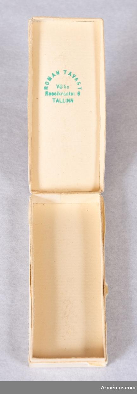 Grupp: M. Frihetskorset tredje graden andra klassen (tapperhet lägsta graden). Formen och storleken på denna dekoration är lika dem, som finnas angivna under no 16330, men detta ordenstecken, skiljer sig från det förra genom att korset består av oxiderat järn, att armarnas ytterlinjer inte äro upphöjda, att den i mitten befintliga upphöjningens kant är av silver på båda sidor samt att mittfältet består av röd refflad emalj. Bandet är till bredd och utseende lika med bandet till no 16330 med den skillnad, att mittpartiet här är mellanblått samt att de yttersta smala ränderna äro svarta i stället för blå. Beskrivning se no 16330.