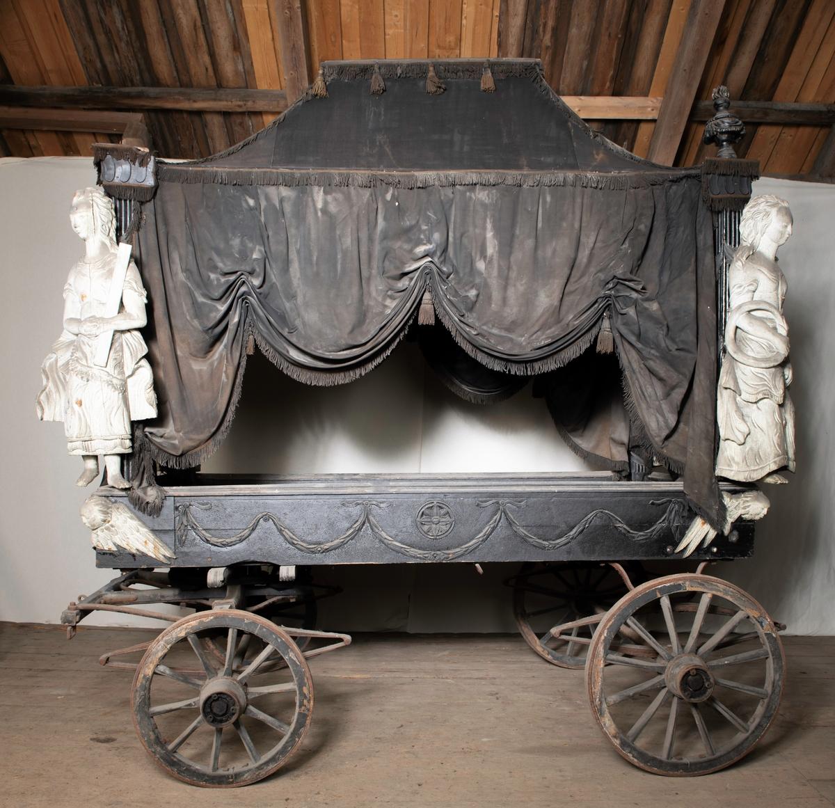 Likvogn med sort firkantet fating dekorert med blomster og guirlandere på sidene. I hvert av fatingens hjørner er det et bevinget hode, seraf. I hvert hjørne av vognen er det en skulptur i form av kvinne. Hver holder et attributt. Skulpturene er i utskåret tre, hvitmalte. Vognen er drapert med sort tekstil med frynser langs kantene og possementer. To av hjørnene på toppen har utskårne urneformer med fakler. To mangler. Sekundært understell. Dette ser ut til å være produsert til – eller tilpasset – vognen. Undervognen er fra etter 1900 (jf. sekskantmuttere). Tre hjulmeier funnet, antatt tilhørende likvognen, men de er ikke oppført i museumsprotokollen.