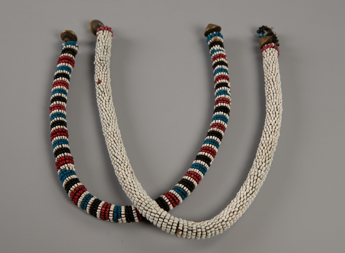 Litt tykk perlesnor med tverrader i sort, hvitt, egyptisk blått og rødt. I hver ende en spiss messingknapp. Hempe mangler.
