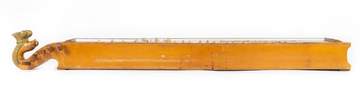 Gjenstanden består av to deler; langeleik med kasse.   Langeleik dekorert med perlemorinnlegg og malte, sorte mønstre. Ender i løvehode med forgylt krone (malt)  Instrumentkassen er laget av tynne treplater, trukket med (imitert?) skinn i mørkerød tone. Stålbeslag i hjørnene. Håndtak. Innvendig er kassen trukket med lilla stoff.