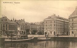 Vykort med motiv över hamnen och ett par passagerarbåtar i S