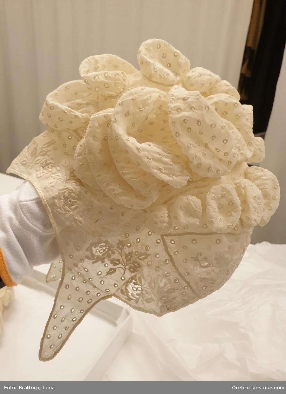 Morgonmössa för dam, av vit batist, broderad. Kullen består av 5 delar: framkant, sid- och nackstycke går i ett, med söm i nacken. Mössan är broderad med vitsöm, med, i blommorna, infällda tyllbottnar. Sidstyckena är långt utdragna i avsmalnande snibbar över öronen. Kullstycket är helt täckt av större och mindre puffar, tätt broderade med tränsade hål. Fållen uppsydd med langett. Från omkring 1804. Okänd proveniens.    Publ: Se Modische Eleganz, bild 22.
