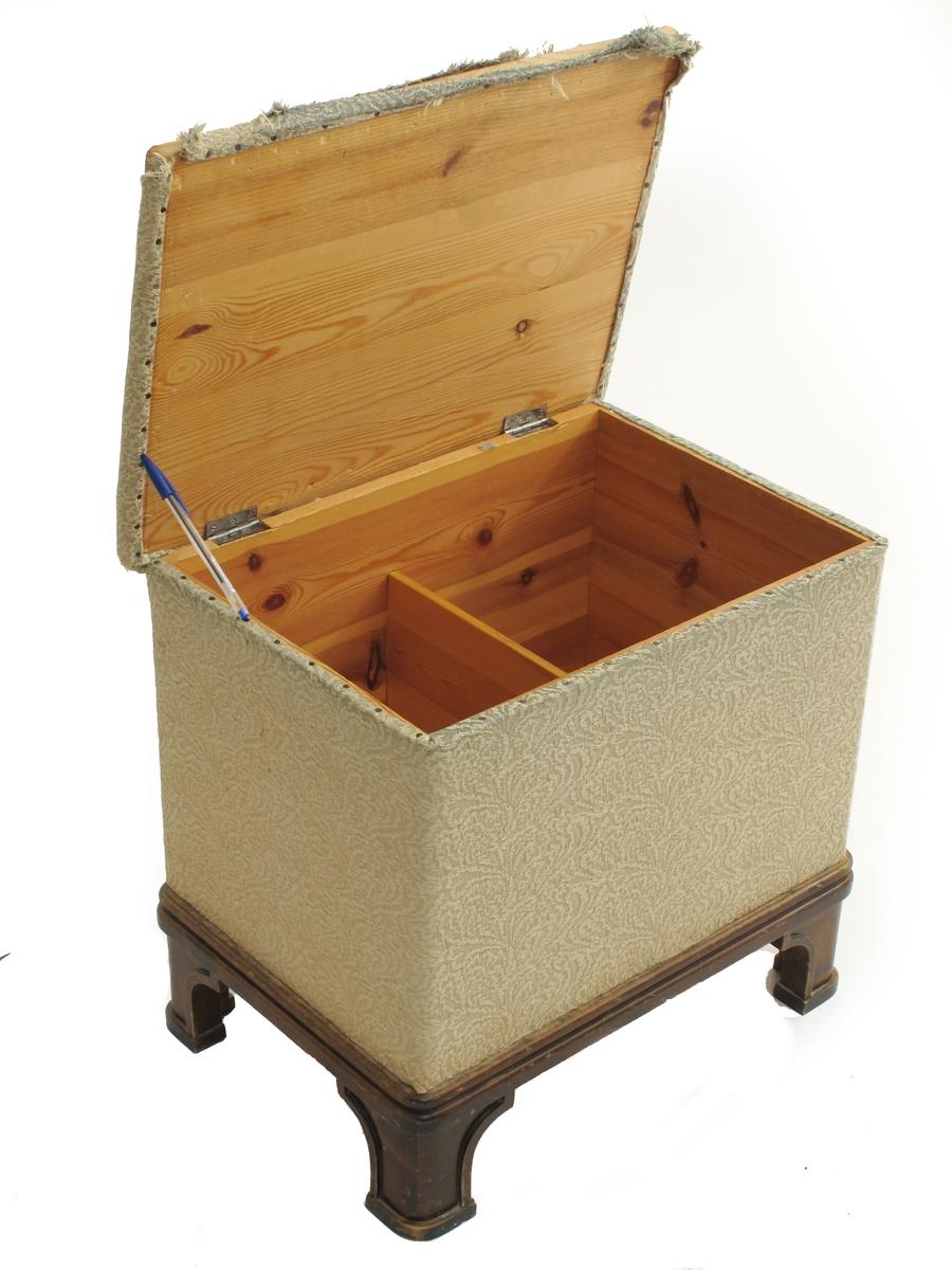 Kasse med lokk, på bein. Sete / lokk trukket med tekstil. Tilstand: Noe slitt trekk, langs forkant helt utslitt.