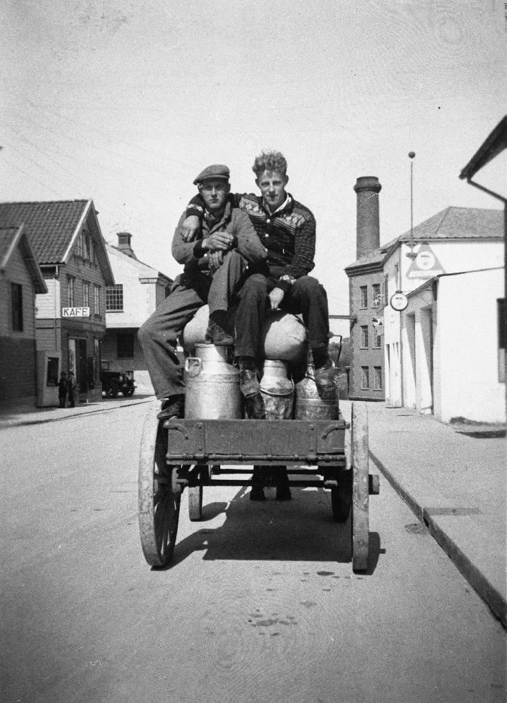 Mjølkekjøring med hest og kjerre i enden av Storgata mot mølla. Til v. Ruglandskafeen. Til høgre Bryne mølle og Bolme sin bensinstasjon. Til venstre i kjerra sit Arne Herigstad, Kåsen og Jonas Salte, Salte.