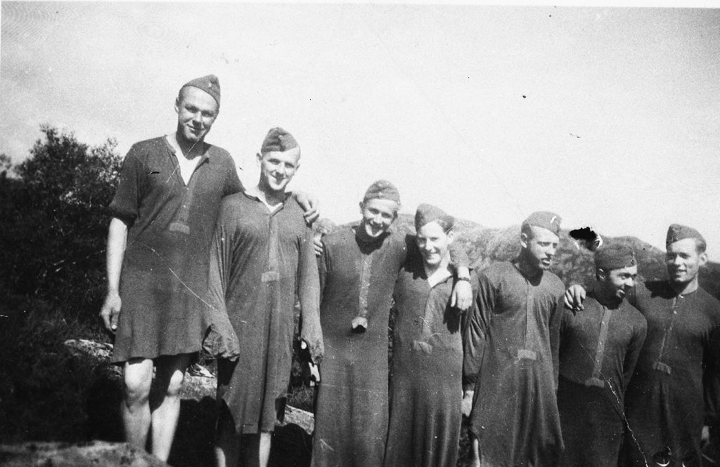 Sju menn frå AT - Arbeidstjenesten fotografert i underskjorta. Frå v. Einar Rage, nr. 5 Johannes Myklebust, nr. 6 Andersen. Dei andre er ukjende.