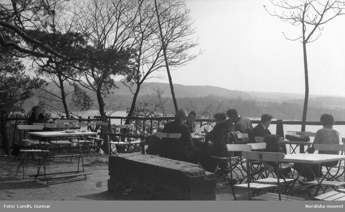 Motiv: Utlandet, Märkische Schweiz 102 - 108 ; Kvinnor och män sitter på en uteservering vid en sjö, landskapsvy med träd - vass och sjö.