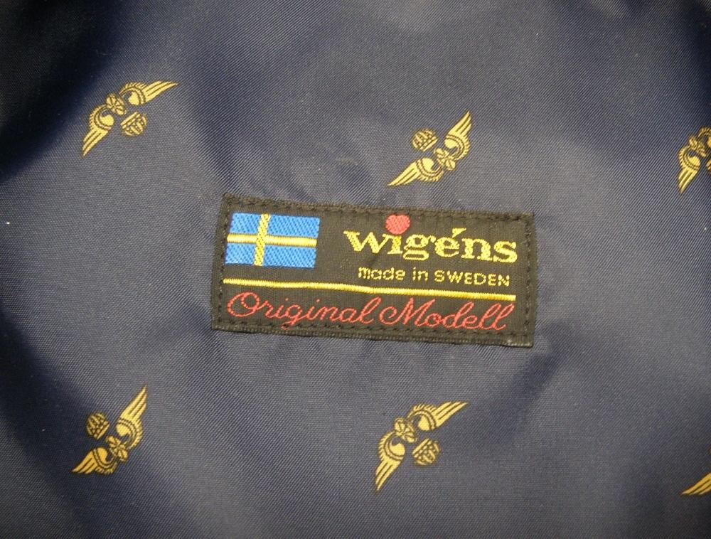 Skärmmössa med lågt kapell av vintertyg och mörkblått mössband. Guldfärgad stormträns och mösstränsknappar (1991). Stort mössmärke av 1991 års modell.