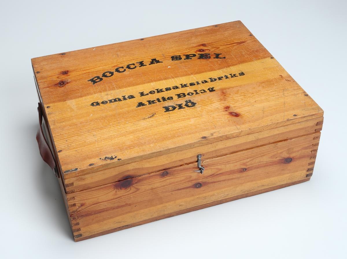 Bocciaspel. Trälåda av lackad furu med sinkade gavlar och bärhandtag av läder. Tryckt text på locket. Lådan innehåller 13 klot, varav ett mindre, rött. På insidan av locket sitter det spelanvisningar.    Inskrivet i huvudboken 1978.