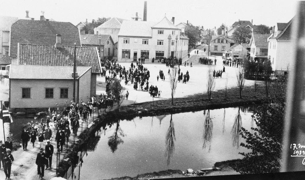 17. mai-toget på brua over Mølledammen i 1933. I bakgrunnen Torget med Jæren Forbruksforening/Domus.