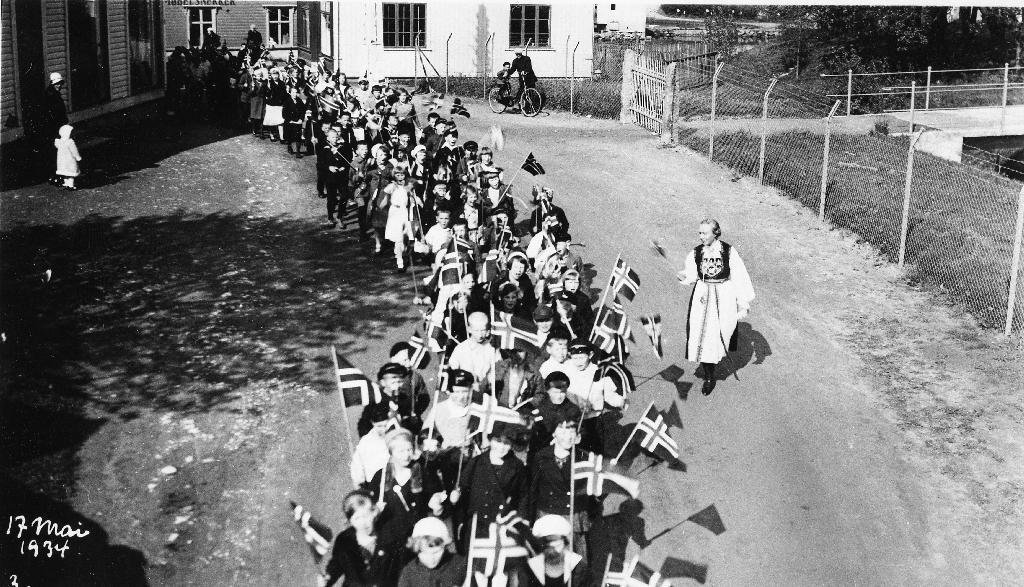 17. mai-tog 1934 i gata, nåverande Arne Garborgs veg, mellom Jæderens Uldvarefabrik og Ullvareutsalget. Til høgre lærar Dagny Tyse i bunad.