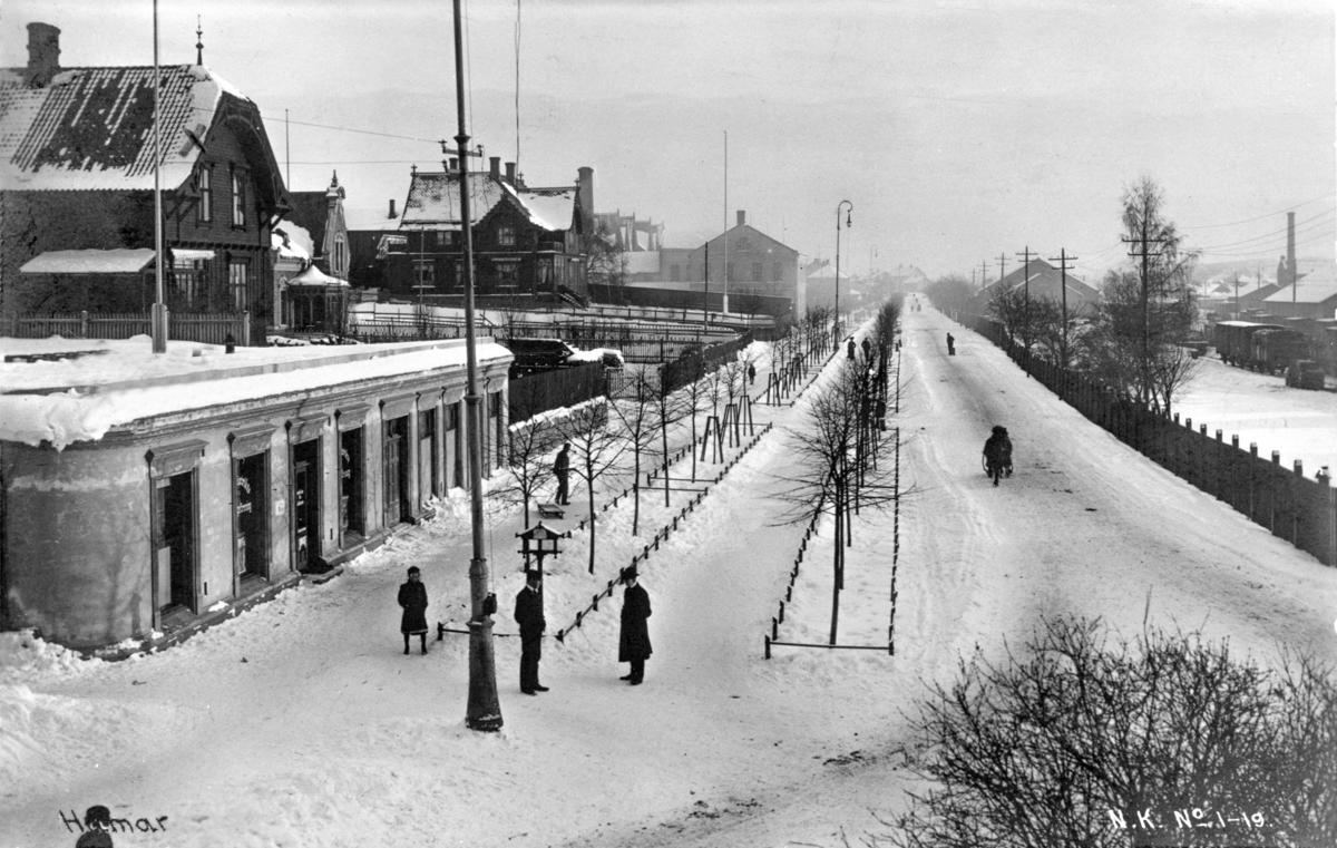Svart-hvitt foto av snøhvit, rett gate som går rett innover i bildet. På høyre side skimtes et gammelt tog, det er noen menn i frakk og hatt som står i vegen, og på venstre side noen staselige trehus og et lavt murbygg med rundt hjørne.