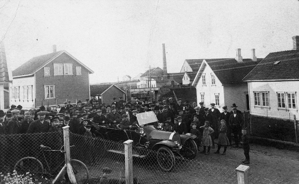Frå austsida av jernbanen på Bryne ca 1900. Mykje folk er samla i samband med vitjing av statsråd Knutsen. Han kjøyrer i bilen til O. G. Kverneland.