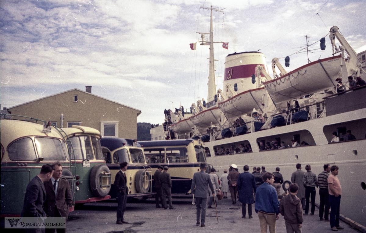 """Varna ankommer Molde..""""Varna"""" : Bygd i 1951 som """"Ocean Monarch"""" for Furness Withy, England, 51-67 : """"Ocean Monarch"""",.67-77 : """"Varna"""", Navigation Maritime Bulgare, Sofia, Bulgaria, operert av Balkanturist i 67-73, men stort sett opplagt i 70-78..Bussene med registreringsnummer T-8606 og T-8608 tilhørte Kleive Auto, med karakteristiske farger, grønn under vinduene og gul overdel. Bak disse ser vi bakenden på to busser i mørkblå og gult. Dette var busser fra Aarø og Molde Auto eller Hjelset Auto."""