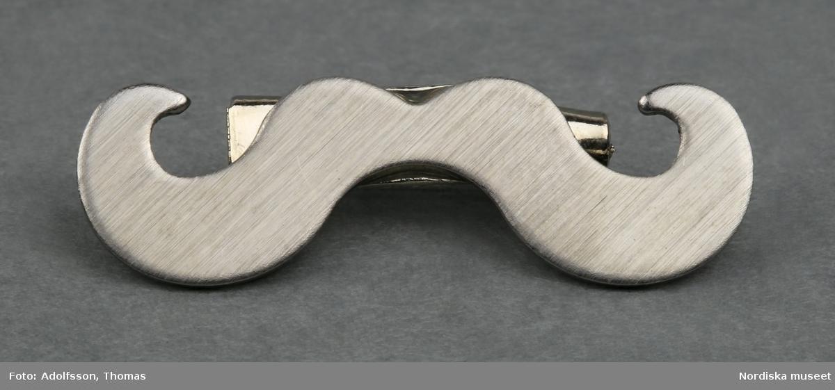 a-b) a) Brosch / pin i vit metall. Form av en mustasch med lätt uppböjda ändar. På baksidan en säkerhetsnålsliknande anordning för broschens fästande på klädesplagg.  Broschen är i original fästad på b) en liten informationsfolder om Prostatacancer, forskningsläget och insamlingen till Mustaschkampen.   /Cecilia Wallquist 2013-09-04.
