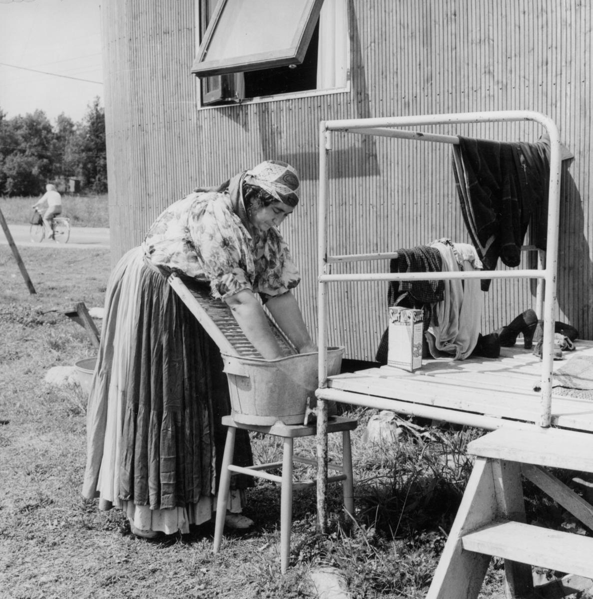 En romsk kvinnar tvättar utanför sin bostadsvagn i Tantolunden, Stockholm. Invid Årstabrons fäste låg ett hus på Tantogatan 26. Strax efter krigsslutet hade Sven Andersson skrivit till fastighetsförvaltningen angående romernas situation varpå den gamla disponentsvillan ställdes till förfogande för svenska romer. Masonitplattor sattes upp för att dela upp huset i lägenheter. Huset var mycket slitet och flera som bott här beskriver råttornas närvaro som påtaglig. Kring huset kom bostadsvagnar att sättas upp. I mitten av 1940-talet rörde sig här mycket folk, både de som bodde här och deras besökare. Vid lägret i Tanto spelades kortfilmen Uppbrott in 1948, med Katarina Taikon i huvudrollen. Vid mitten av 1950-talet hade samtliga boende fått andra bostäder och disponentsvillan revs.