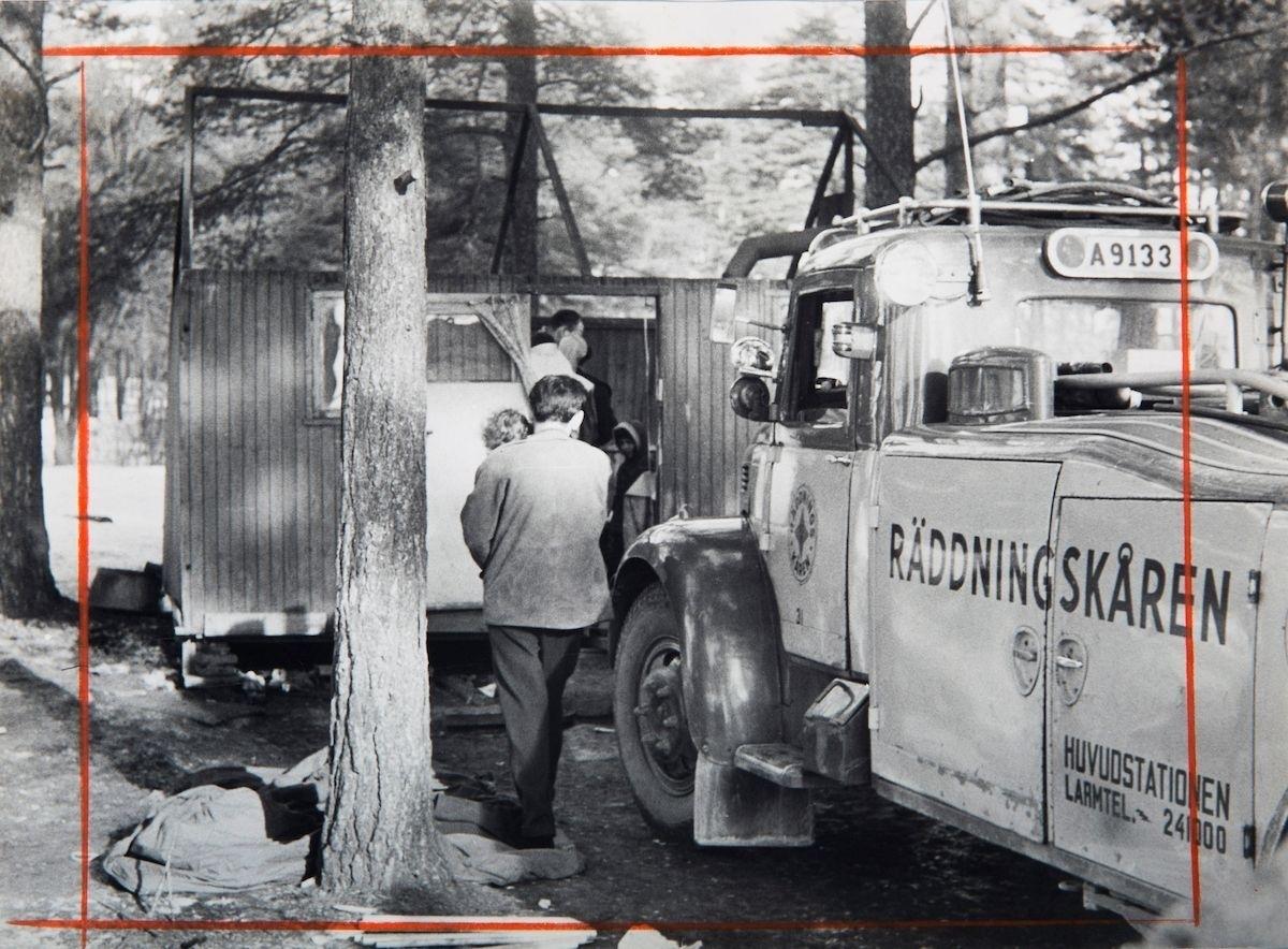 BIlden är tagen i samband med en vräkning av romer i Lilla Sköndal, Stockholm år 1959. Bildtexten uppger att socialborgarrådet Inga Thorsson tagit strid med stadens fastighetskontor, och krävt garantier för att liknande händelser inte återupprepas. Vid Lilla Sköndal har romska boplatser i olika former funnits åtminstone sedan år 1943, då staden iordningsställde en lägerplats. Lägret låg då vid en bergsknalle vid Skogskyrkogårdens södra del och år 1944 bodde här ett trettiotal personer. De boende fick hämta vatten hos några boende i närheten. Efter att de svenska romerna i Sverige erkändes som medborgare år 1952 uppstod debatt kring gruppens svåra levnadsförhållanden. En statlig utredning genomfördes under 1954-1956 där en av slutsatserna blev att fast bostad var nyckeln till att lyckas med skolgång och arbetsliv. Efter att även Stockholm stad genomfört en utredning (1955-57) upprättades två lägerplatser vid Flaten, samt en försöksverksamhet med provisoriska bostäder i Hammarbytäppan. Tanken var att romerna skulle bo här tills dess att bostadsfrågan löstes. De två lägerplatserna vid Skarpnäck låg med omkring 2 kilometers mellanrum. De kom att benämnas Ekstubben respektive Skarpnäckslägret. Skarpnäckslägret stod färdigt för inflytt i oktober 1959 och Ekstubben stod färdig för inflyttning 15 mars 1960. Lägren skulle finnas under en övergångsperiod innan fasta bostäder ordnats, men i realiteten drog bostadsfrågan ut på tiden och lägren blev kvar i fem år. Detta trots att kommuner från och med mars 1960 hade möjlighet att rekvirera statsbidrag för kostnader i samband med romers bosättning. Även denna process blev utdragen och det tog flera år innan fast bostad kunde erbjudas till alla svenska romer.