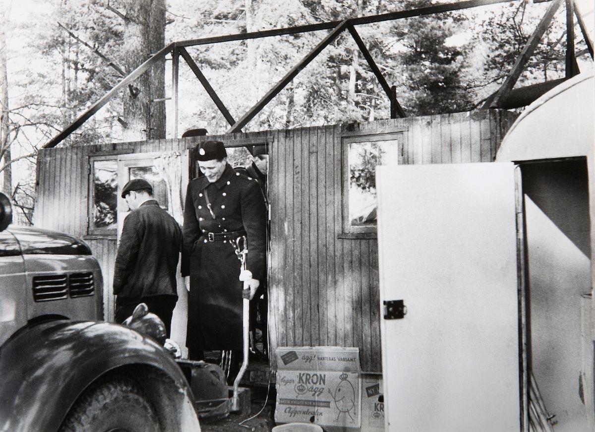 BIlden är troligen tagen i samband med en vräkning av romer i Lilla Sköndal, Stockholm år 1959. Vid Lilla Sköndal har romska boplatser i olika former funnits åtminstone sedan år 1943, då staden iordningsställde en lägerplats. Lägret låg då vid en bergsknalle vid Skogskyrkogårdens södra del och år 1944 bodde här ett trettiotal personer. De boende fick hämta vatten hos några boende i närheten. Efter att de svenska romerna i Sverige erkändes som medborgare år 1952 uppstod debatt kring gruppens svåra levnadsförhållanden. En statlig utredning genomfördes under 1954-1956 där en av slutsatserna blev att fast bostad var nyckeln till att lyckas med skolgång och arbetsliv. Efter att även Stockholm stad genomfört en utredning (1955-57) upprättades två lägerplatser vid Flaten, samt en försöksverksamhet med provisoriska bostäder i Hammarbytäppan. Tanken var att romerna skulle bo här tills dess att bostadsfrågan löstes. De två lägerplatserna vid Skarpnäck låg med omkring 2 kilometers mellanrum. De kom att benämnas Ekstubben respektive Skarpnäckslägret. Skarpnäckslägret stod färdigt för inflytt i oktober 1959 och Ekstubben stod färdig för inflyttning 15 mars 1960. Lägren skulle finnas under en övergångsperiod innan fasta bostäder ordnats, men i realiteten drog bostadsfrågan ut på tiden och lägren blev kvar i fem år. Detta trots att kommuner från och med mars 1960 hade möjlighet att rekvirera statsbidrag för kostnader i samband med romers bosättning. Även denna process blev utdragen och det tog flera år innan fast bostad kunde erbjudas till alla svenska romer.