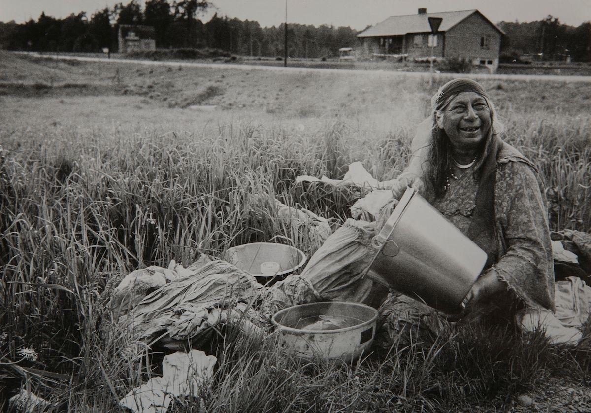 I kanten av en äng sitter en kvinna med sin tvätt. I bakgrunden syns en landsväg och ett hus. Toleransen för romer har historiskt varierat mycket mellan olika samhällen, men romers närvaro har sällan setts som något positivt. Ofta fick man slå sig ned i samhällets utkant, man har förvägrats fast bostad och fördrivits. Hur ofta man fick stanna på en plats var olika från kommun till kommun, men sällan längre än tre veckor. Tillgången till vatten var olika beroende på var man fick slå sig ned. Att tvätta var ofta mycket arbetssamt och krävde mycket arbete.
