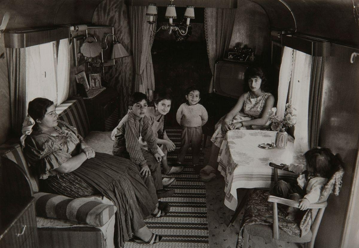 Två kvinnor och en samling barn sitter i en bostadsvagn. Bilden är tagen i Skarpnäck, troligen  i något av de läger som irodningsställdes av Stockholms stad i slutet av 1950-talet. Efter att de svenska romerna i Sverige erkändes som medborgare år 1952 uppstod debatt kring gruppens svåra levnadsförhållanden. En statlig utredning genomfördes under 1954-1956 där en av slutsatserna blev att fast bostad var nyckeln till att lyckas med skolgång och arbetsliv. Efter att även Stockholm stad genomfört en utredning (1955-57) upprättades två lägerplatser vid Flaten, samt en försöksverksamhet med provisoriska bostäder i Hammarbytäppan. Tanken var att romerna skulle bo här tills dess att bostadsfrågan löstes. De två lägerplatserna vid Skarpnäck låg med omkring 2 kilometers mellanrum. De kom att benämnas Ekstubben respektive Skarpnäckslägret. Skarpnäckslägret stod färdigt för inflytt i oktober 1959 och Ekstubben stod färdig för inflyttning 15 mars 1960. Lägren skulle finnas under en övergångsperiod innan fasta bostäder ordnats, men i realiteten drog bostadsfrågan ut på tiden och lägren blev kvar i fem år. Detta trots att kommuner från och med mars 1960 hade möjlighet att rekvirera statsbidrag för kostnader i samband med romers bosättning. Även denna process blev utdragen och det tog flera år innan fast bostad kunde erbjudas till alla svenska romer.