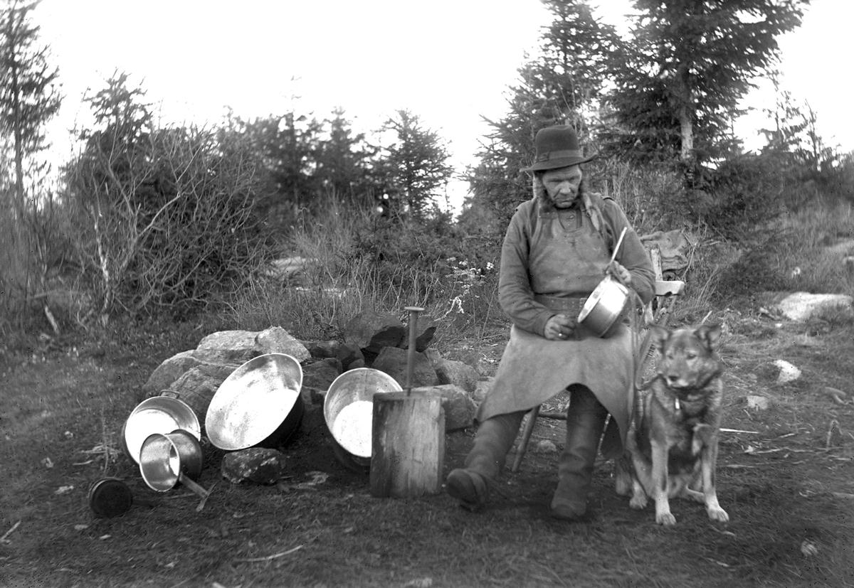 """På bilden syns """"Stor-Johan"""", förtennare och kopparslagare. Enligt Per Asplunds artikel i Hälsingerunor (1954) var Johan av resandesläkt och ska ha rest i hela Skandinavien och Finland.  Då han blev äldre arbetade han främst i Dalarna och Hälsingland. Då återkom han till vissa gårdar för härbärge och gjorde därifrån utflykter för att samla in kärl i bygden som skulle repareras. På sommaren lastade han redskapen på en vagn, om vintern på en kälke. Johan var känd för att göra ett bra arbete och berättade gärna om platser han besökt. Arbete med metallhantverk som förtenning och kopparslageri har historiskt varit vanligt bland resande i Sverige och Norge."""