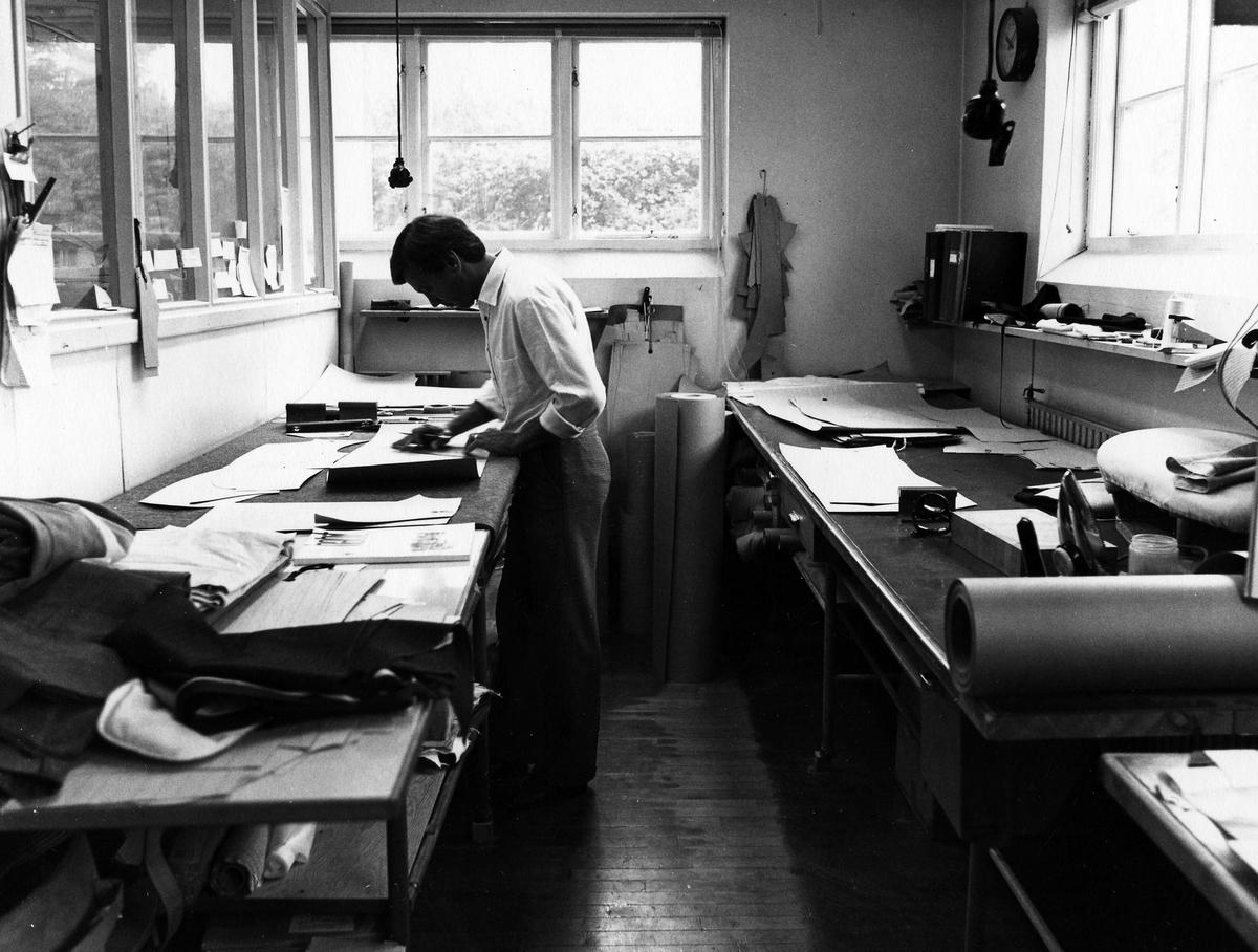 """En man står och arbetar vid ett bord på tillskärningen """"Skärets"""" designavdelning i bottenvåningen på Drabant AB."""