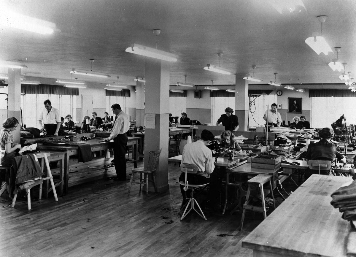 En grupp kvinnor och män arbetar med tillverkning av byxor. Drabant AB:s byxavdelning.