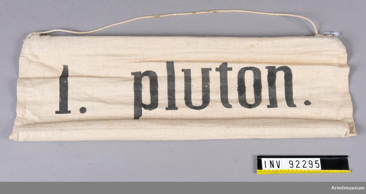 Skylt av tyg med träpinnar i sydda kanaler på långsidorna. Upphängningssnöre. Svart text: 1. Pluton.